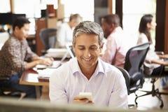 Hombre de negocios Working At Desk que usa el teléfono móvil Foto de archivo