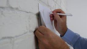 Hombre de negocios Write un aviso en un trozo de papel en la pared de la oficina metrajes