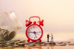 Hombre de negocios y despertador rojo en la pila de monedas en el concepto de ahorros y de crecimiento del dinero o de reserva de imagen de archivo