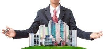Hombre de negocios y edificio moderno en el uso del campo de hierba verde para el tema de la gestión de la tierra Imágenes de archivo libres de regalías