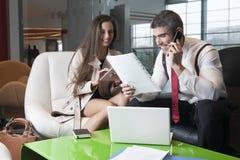 Hombre de negocios y empresaria en la reunión con el ordenador portátil y la tableta foto de archivo libre de regalías