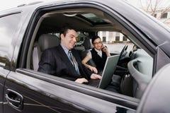 Hombre de negocios y empresaria en un coche Imágenes de archivo libres de regalías