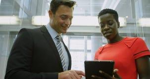 Hombre de negocios y empresaria que discuten sobre la tableta digital en el elevador 4k metrajes