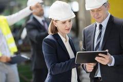 Hombre de negocios y empresaria que usa la tableta digital con los colegas en fondo en la industria imágenes de archivo libres de regalías
