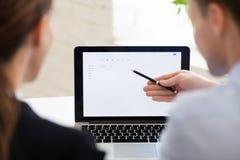 Hombre de negocios y empresaria serios que usa el ordenador portátil, maqueta blanca imágenes de archivo libres de regalías