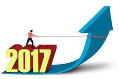 Hombre de negocios y flecha ascendente de los tirones de los números 2017 Imágenes de archivo libres de regalías