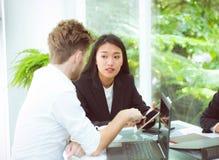 hombre de negocios y gente de la mujer que hace la reunión y que mira la tableta Imagen de archivo