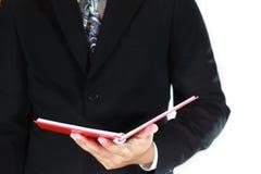 Hombre de negocios y libro rojo Fotografía de archivo libre de regalías