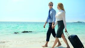 Hombre de negocios y mujer de negocios con una maleta que camina a lo largo de la playa blanca de la arena en la isla almacen de metraje de vídeo