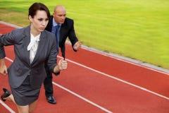 Hombre de negocios y mujer en el funcionamiento en circuito de carreras Imagen de archivo libre de regalías