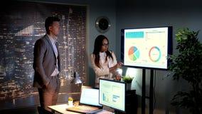 Hombre de negocios y mujer de los businees que analiza el crecimiento de la compañía representado en infographic almacen de video