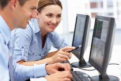 Hombre de negocios y mujer que trabajan en los ordenadores foto de archivo libre de regalías