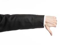 Hombre de negocios y tema del gesto: un hombre en un traje negro y una camisa blanca que muestran gesto de mano en un fondo blanc Fotos de archivo libres de regalías