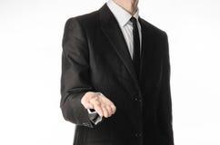 Hombre de negocios y tema del gesto: un hombre en un traje y un lazo negros lleva a cabo hacia fuera su mano aislada en un fondo  Imagen de archivo libre de regalías