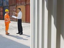 Hombre de negocios y trabajador con los contenedores para mercancías Imágenes de archivo libres de regalías