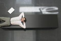 Hombre de negocios Yawning While Lying en banco en oficina fotografía de archivo