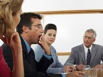 Hombre de negocios Yawning During Meeting en la sala de conferencias Imagen de archivo libre de regalías