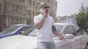 Hombre de Oriente Medio calvo confiado acertado hermoso del retrato que habla por el teléfono celular que coloca después su coche almacen de metraje de vídeo