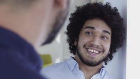 Hombre de Oriente Medio de mirada fresco con la charla afro en oficina almacen de metraje de vídeo