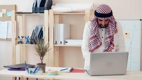 Hombre de Oriente Medio moderno en el traje étnico que trabaja en la oficina en el escritorio hombre de negocios con ghutra en su metrajes
