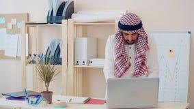 Hombre de Oriente Medio moderno en el traje étnico que trabaja en la oficina en el escritorio hombre de negocios con ghutra en su almacen de video
