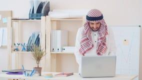 Hombre de Oriente Medio moderno en el traje étnico que trabaja en la oficina en el escritorio hombre de negocios con ghutra en su almacen de metraje de vídeo