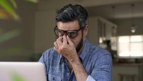 Hombre de Oriente Medio subrayado que trabaja en el ordenador metrajes