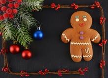 Hombre de pan de jengibre que miente en fondo oscuro La Navidad o composición del Año Nuevo Tarjeta de Navidad Fotografía de archivo