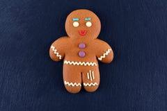 Hombre de pan de jengibre que miente en fondo oscuro La Navidad o composición del Año Nuevo Tarjeta de Navidad Foto de archivo