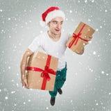 Hombre de Papá Noel que mira para arriba, sosteniendo el regalo foto de archivo