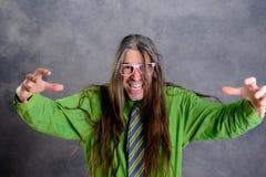 Hombre de pelo largo, enojado en vidrios verdes del rosa de la camisa Imagenes de archivo