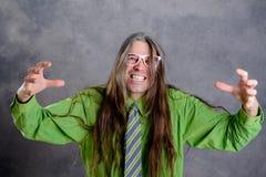 Hombre de pelo largo, enojado en vidrios verdes del rosa de la camisa Foto de archivo libre de regalías