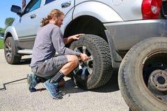 Hombre de pelo largo que cambia su neumático soplado y plano del camión en el Si foto de archivo libre de regalías