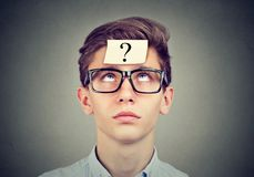 Hombre de pensamiento con el signo de interrogación que mira para arriba Fotografía de archivo