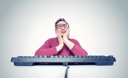 Hombre de pensamiento en vidrios detr?s de un teclado delante de un ordenador, llevando a cabo su cabeza en sus manos Sue?o del p fotos de archivo