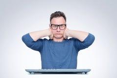 Hombre de pensamiento en vidrios detrás de un teclado delante de un ordenador que mira en la cámara, llevando a cabo su cabeza en fotografía de archivo libre de regalías