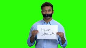 Hombre de piel morena silenciado con la cinta negra sobre boca metrajes