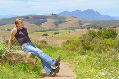 Hombre de relajación contra granja y la montaña imagen de archivo libre de regalías
