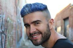 Hombre de risa con el pelo enrrollado azul sobre fondo urbano de la pintada Fotos de archivo libres de regalías
