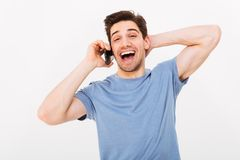 Hombre de risa en camiseta que habla por smartphone mientras que lleva a cabo la cabeza Fotografía de archivo