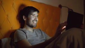 Hombre de risa joven que usa la tableta para practicar surf los medios sociales que mienten en cama en casa antes de dormir Imagen de archivo
