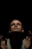 Hombre de rogación aislado en negro imagen de archivo libre de regalías