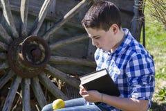 Hombre de Rural.Young que lee un libro en al aire libre con la manzana amarilla. Fotografía de archivo