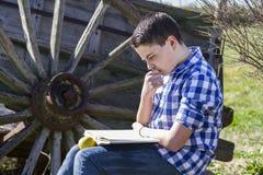Hombre de Rural.Young que lee un libro en al aire libre con la manzana amarilla. RUR Imágenes de archivo libres de regalías