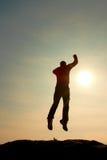 Hombre de salto El hombre loco joven está saltando en fondo colorido del cielo Silueta del hombre de salto y del cielo hermoso de Imagen de archivo