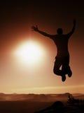 Hombre de salto El hombre loco joven está saltando en fondo rojo del cielo Silueta del hombre de salto Imagen de archivo