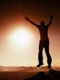Hombre de salto El hombre loco joven está saltando en fondo rojo del cielo Silueta del hombre de salto Foto de archivo