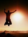 Hombre de salto El hombre loco joven está saltando en fondo rojo del cielo Silueta del hombre de salto Imagen de archivo libre de regalías
