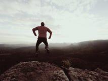 Hombre de salto El hombre loco joven está saltando en cumbre rocosa sobre paisaje Silueta del hombre de salto Imágenes de archivo libres de regalías