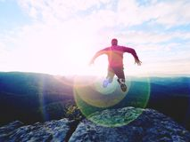 Hombre de salto El hombre loco joven está saltando en cumbre rocosa sobre paisaje Silueta del hombre de salto Imagenes de archivo